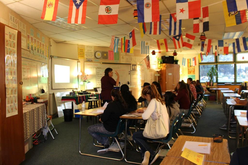 a teacher stands in front of a class with students seated and looking at the teacher and several different flags displayed around the classroom