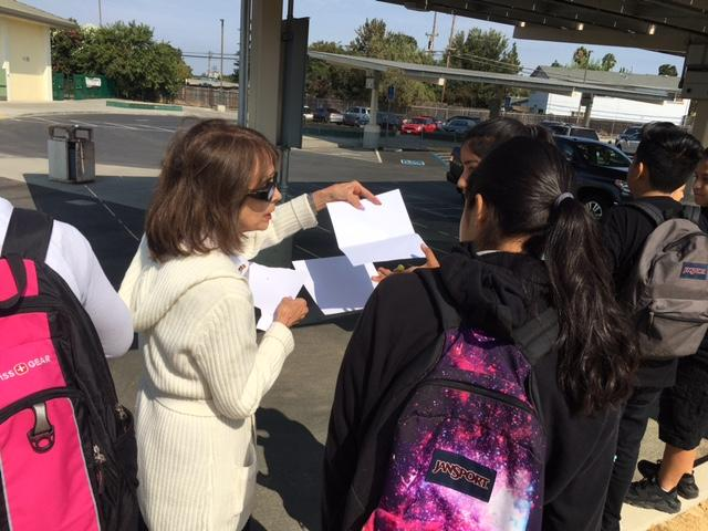 teacher shows students how to use paper to get image of eclipse