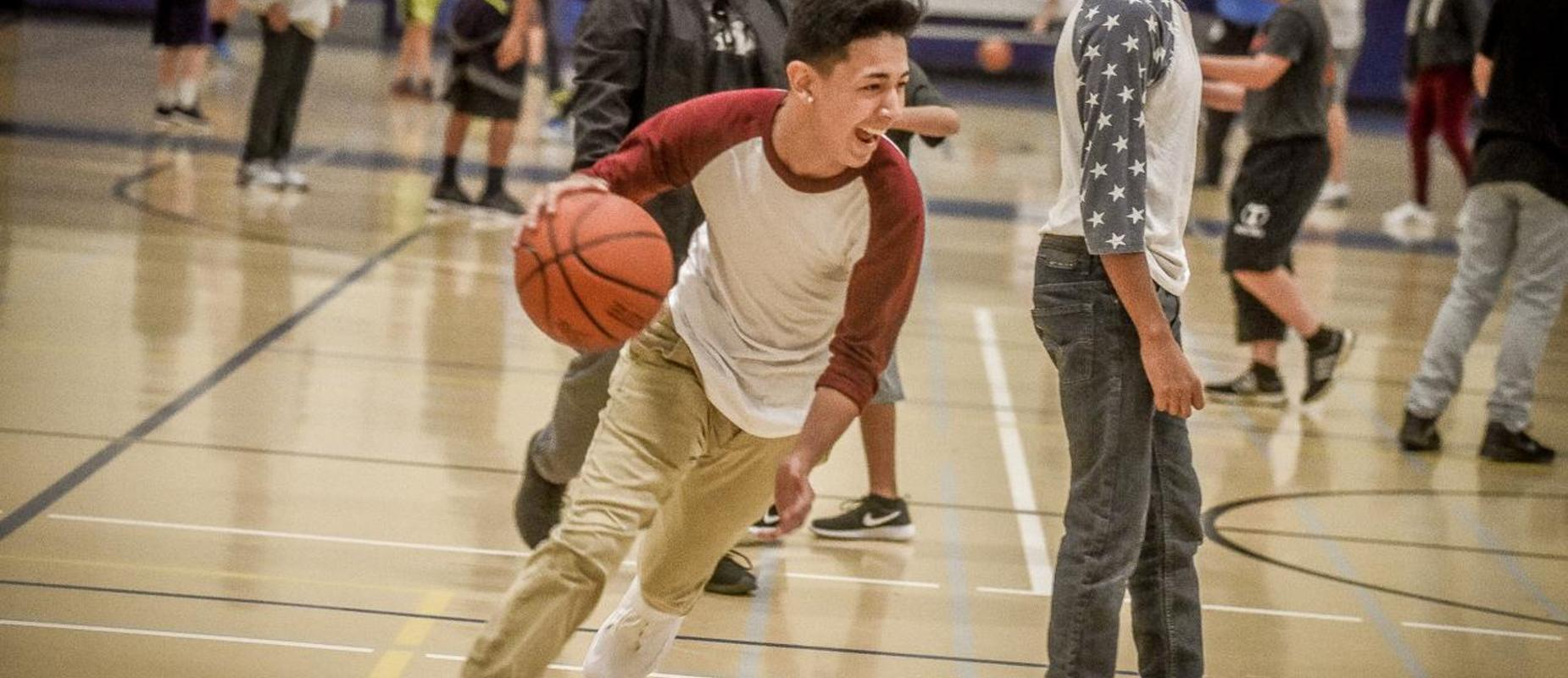 Student laughing and dribbling a basketball