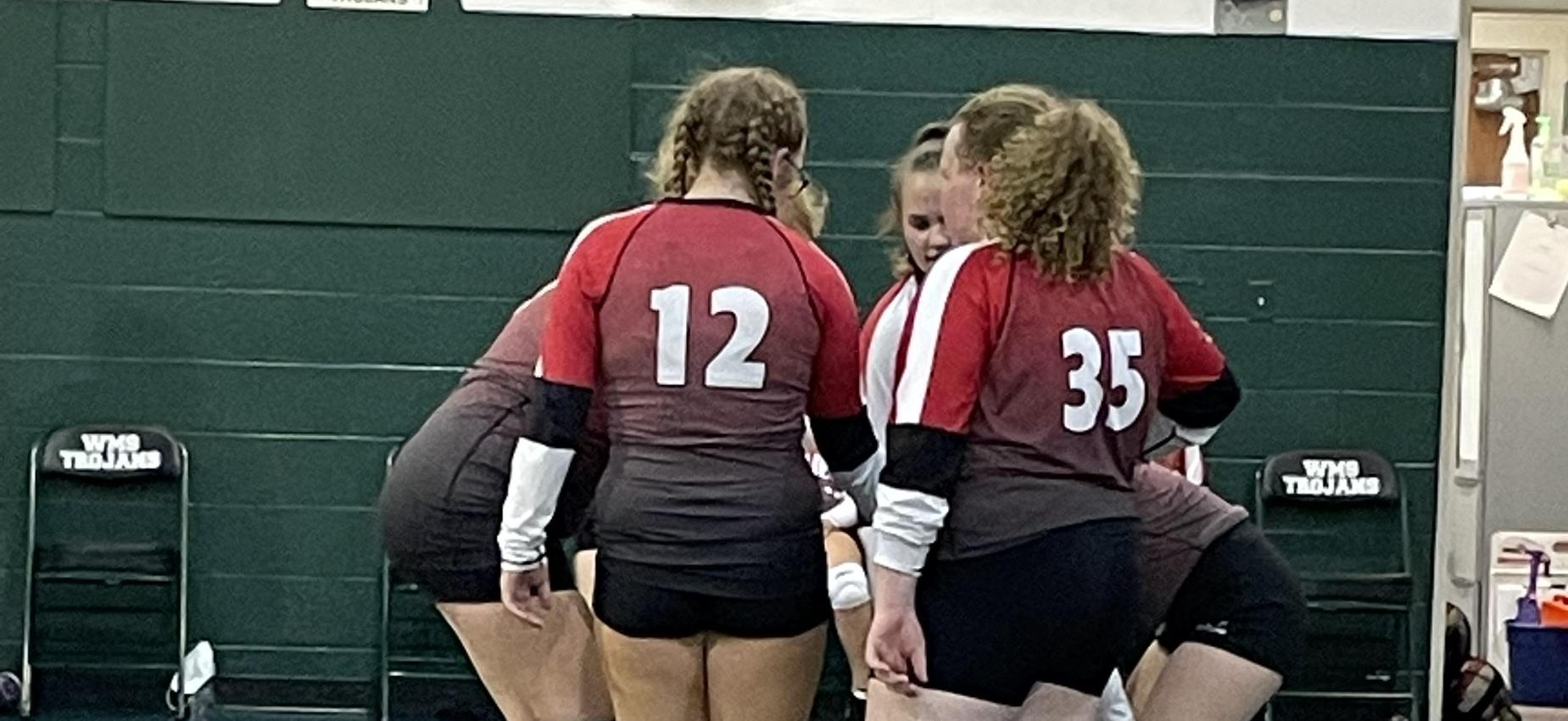 Volleyball players gather in a huddle in a gym.