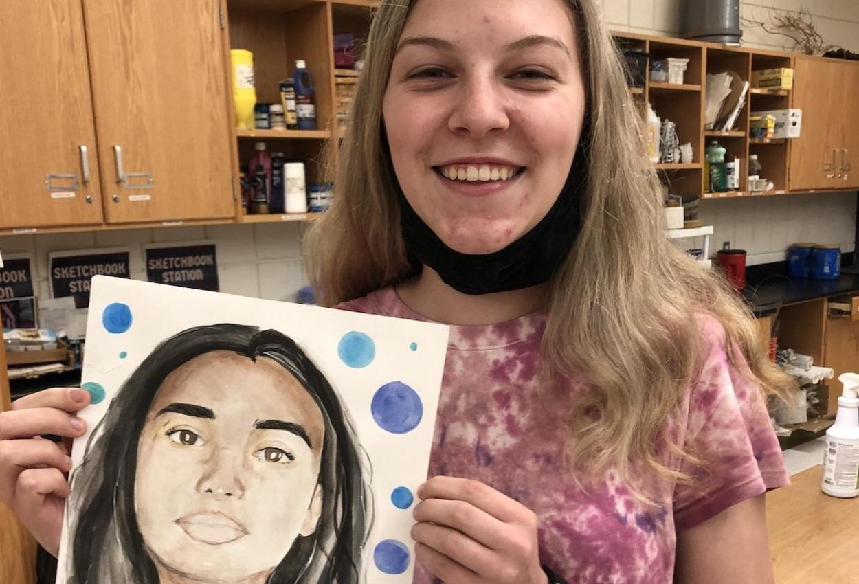 student hold a portrait she created