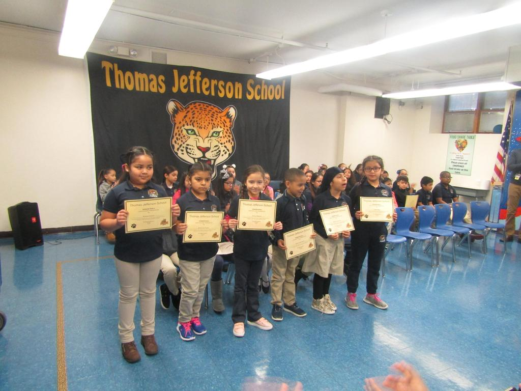 second group of children holding up their honor roll certificates