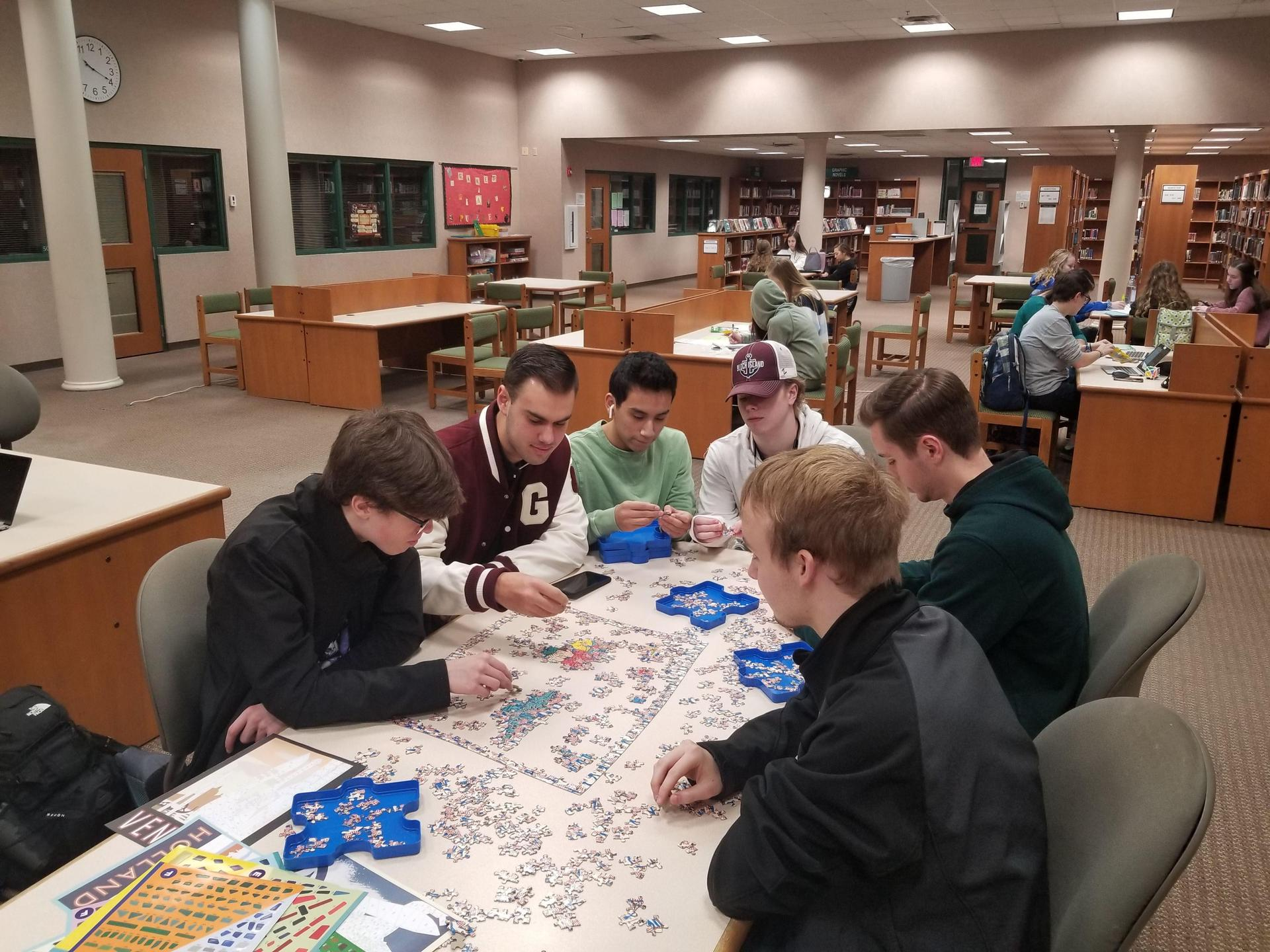 Several male students work on a jigsaw puzzle together at a table