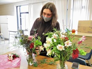 A student creates a floral arrangement during a mental wellness day activity.