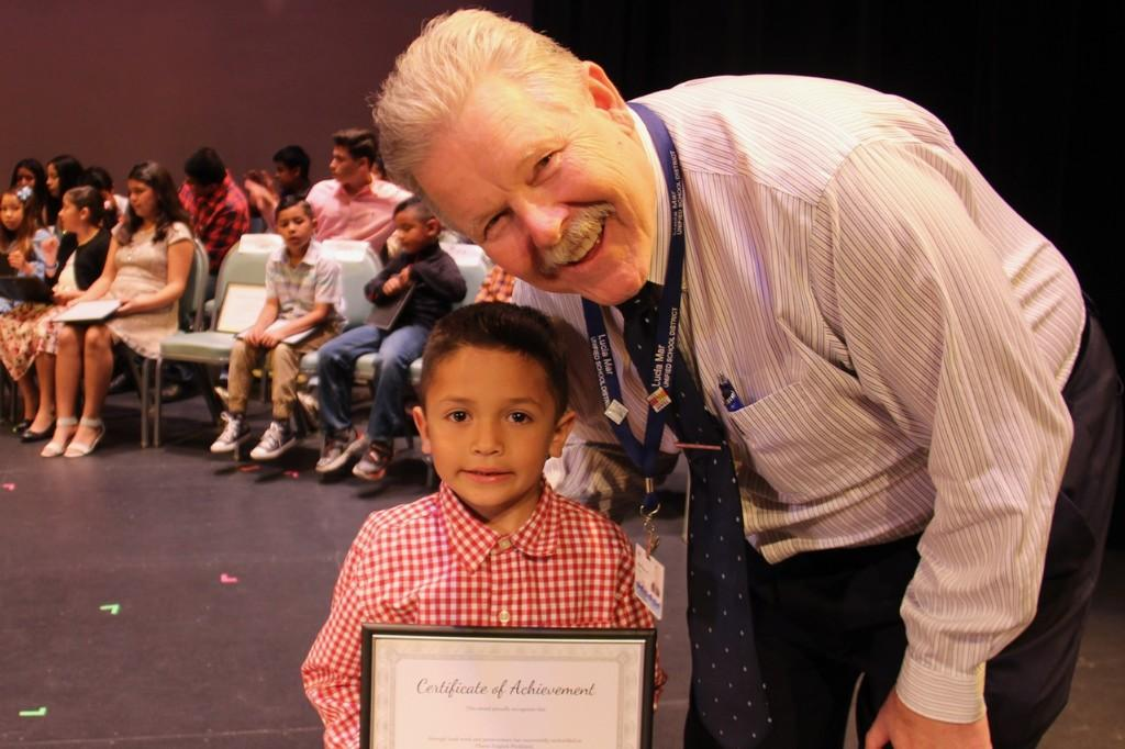 picture of the principal and a student who is receiving a certificate of acheivement