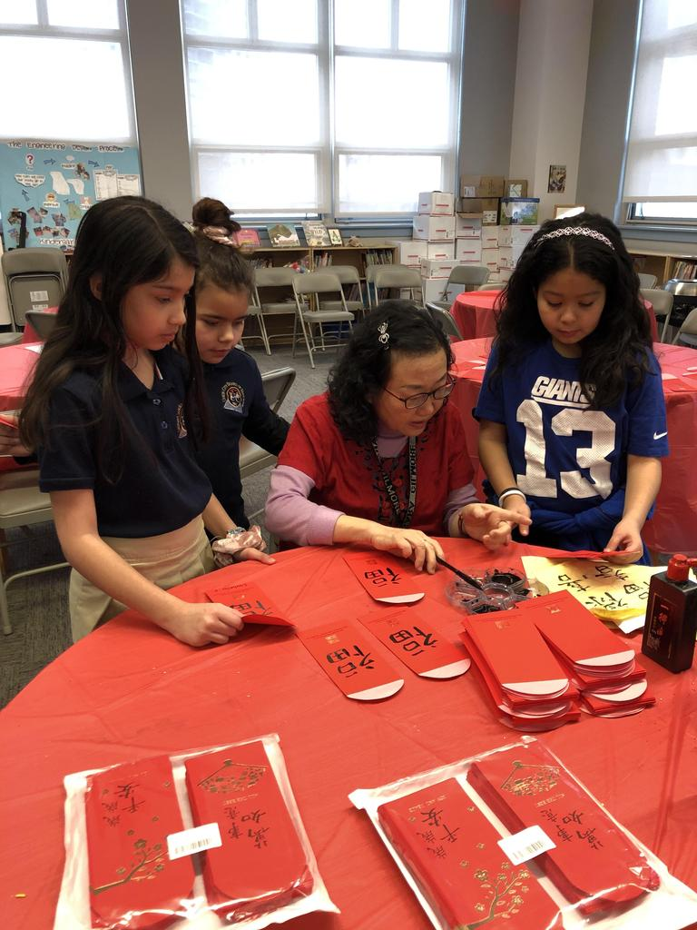 Ms. Chiang teaching the girl how to write letters in Chinese