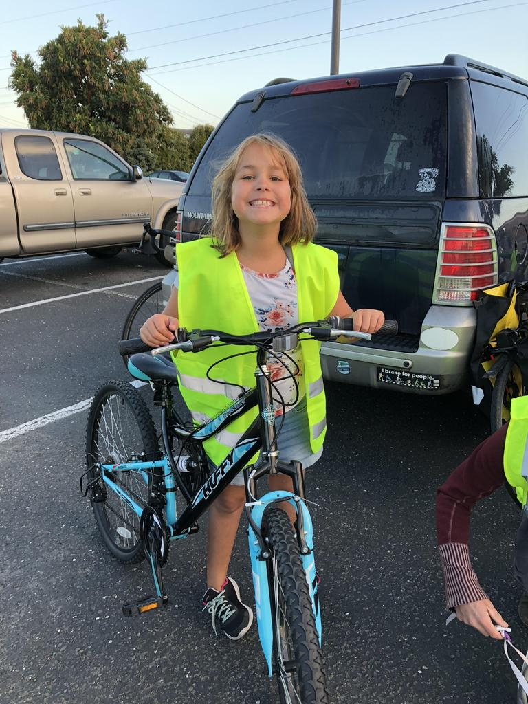smiling student in safety vest with bike