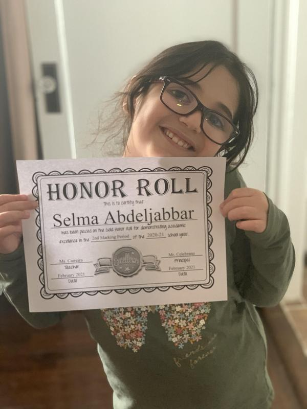 Selma holding honor roll certificate