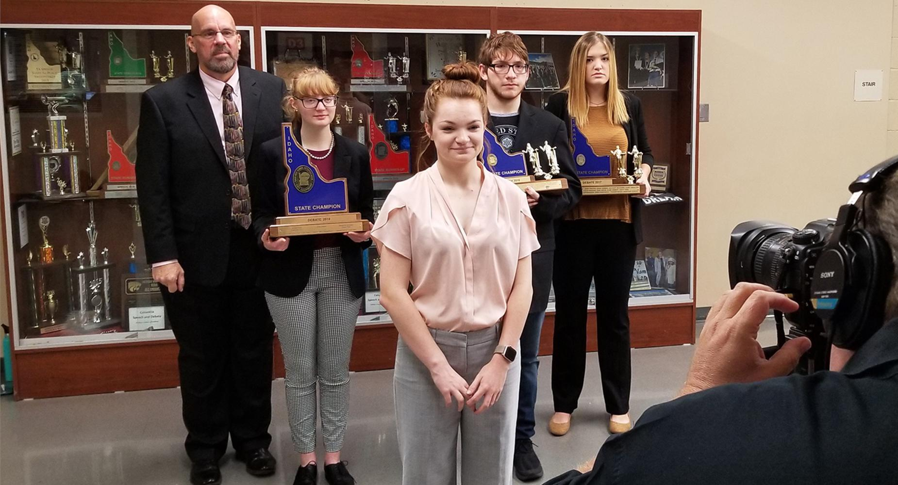Debate coach Jeffrey Stoppenhagen poses with four speech and debate participants and their trophies.