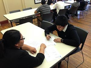 Two students sitting at table writing on a piece of paper.
