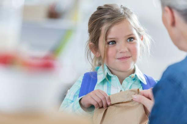 Small girl with a sack lunch