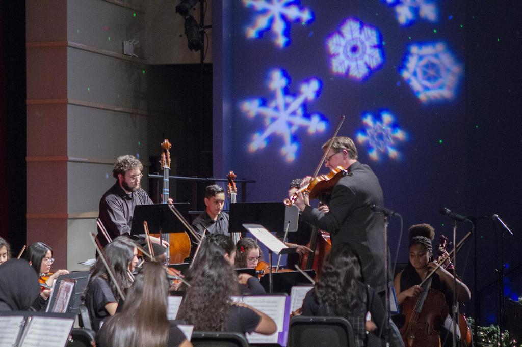 A view of the snowflake light features on the wall of the auditorium with the orchestra performing in the foreground
