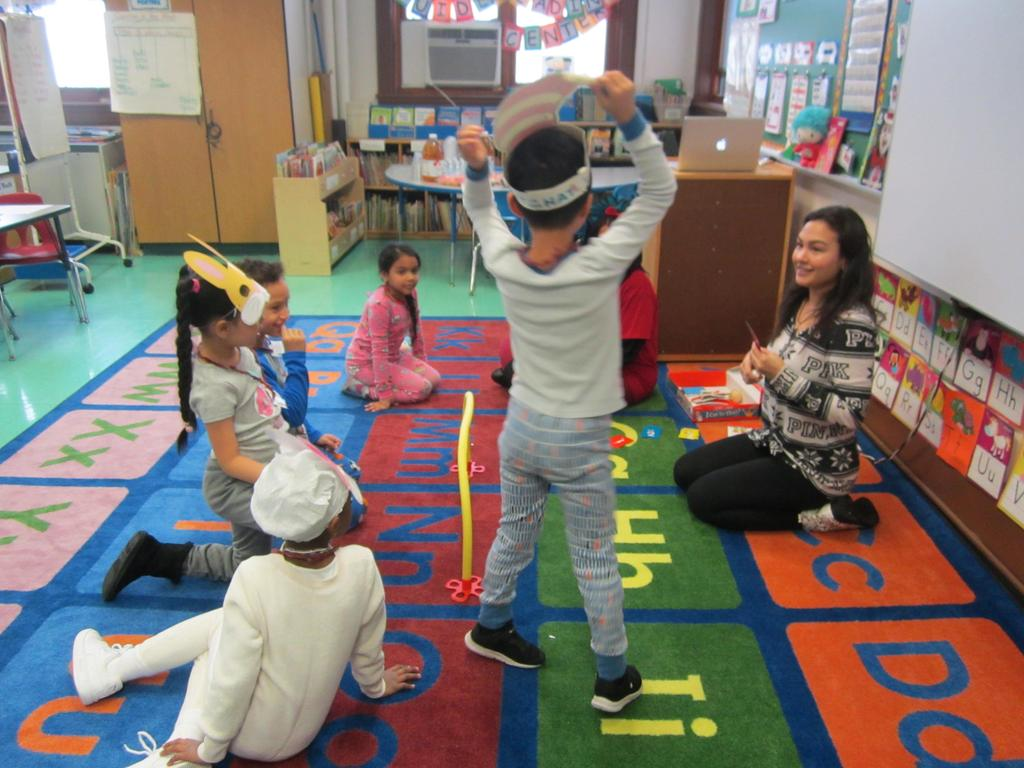 boy in pj's standing up on the class rug with a mom playing a dr. seuss game