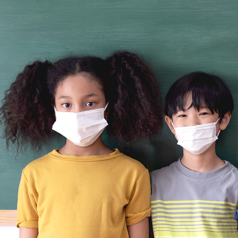 Two students wearing masks, standing in front of a chalkboard