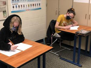 two students write affirmation notes
