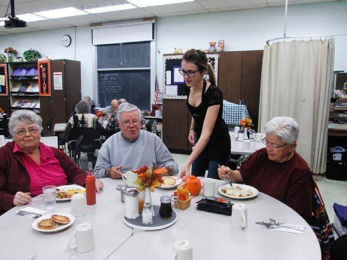 Student serving community members breakfast