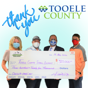 county donates $325,000 to TCSD. Image of Alison McCoy, Shawn Milne, Scott Rogers and Lark Reynolds.