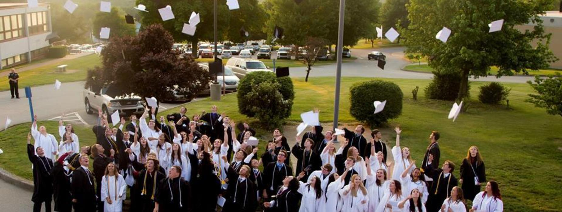 2018 Graduates Outside Throwing their Caps in the Air