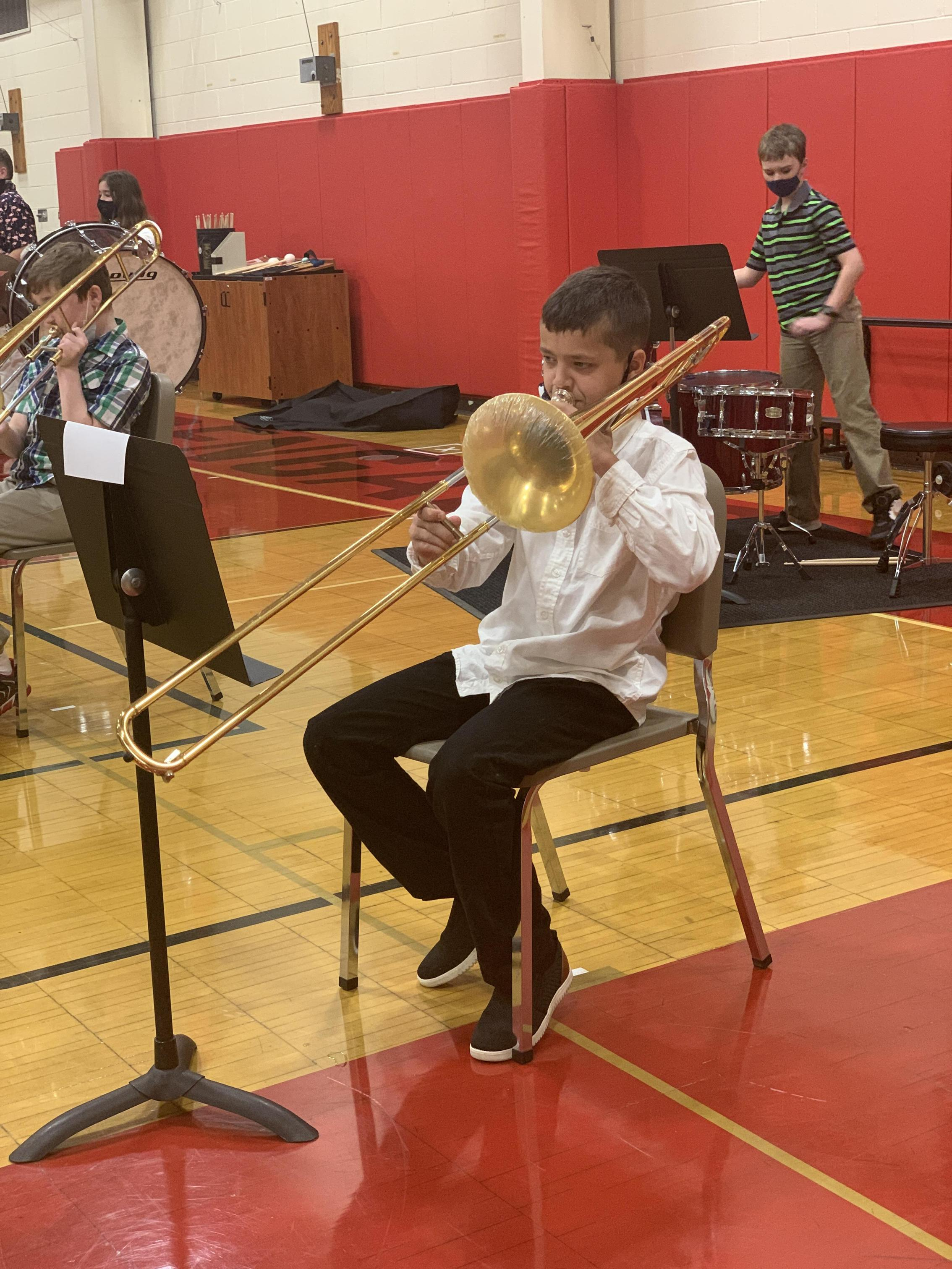 A student playing trombone in the Benjamin gym