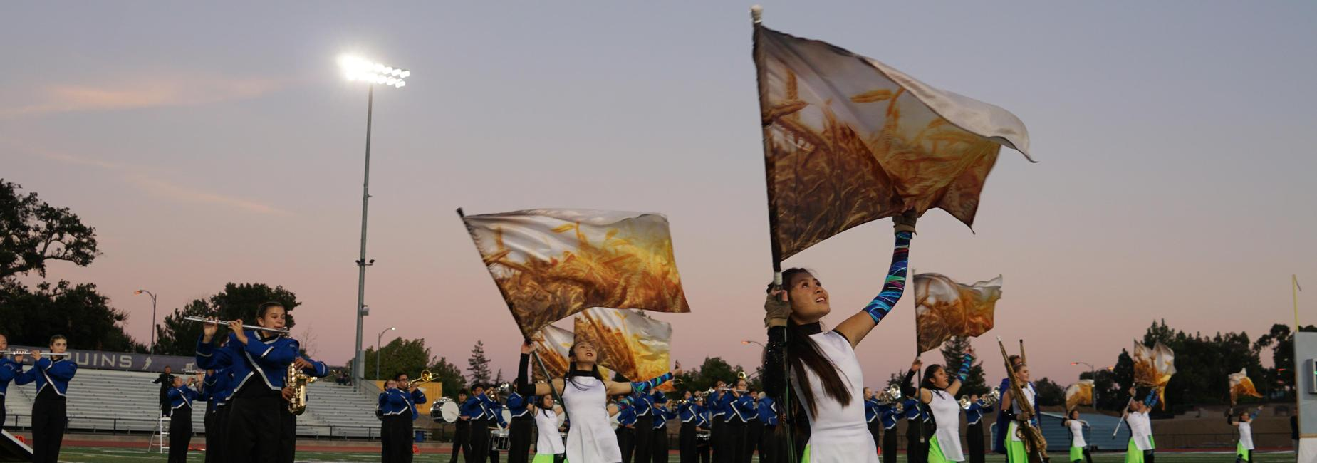 Students playing instruments and moving flags on the football field.