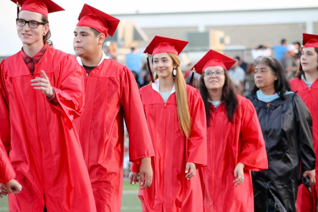 students walk toward the center of memorial stadium to be seated at the 2018 victoria east high school graduation ceremony