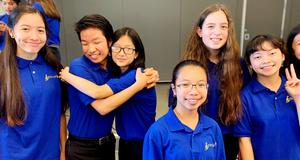 Students from JMS choir poses for camera in their blue polo shirts.