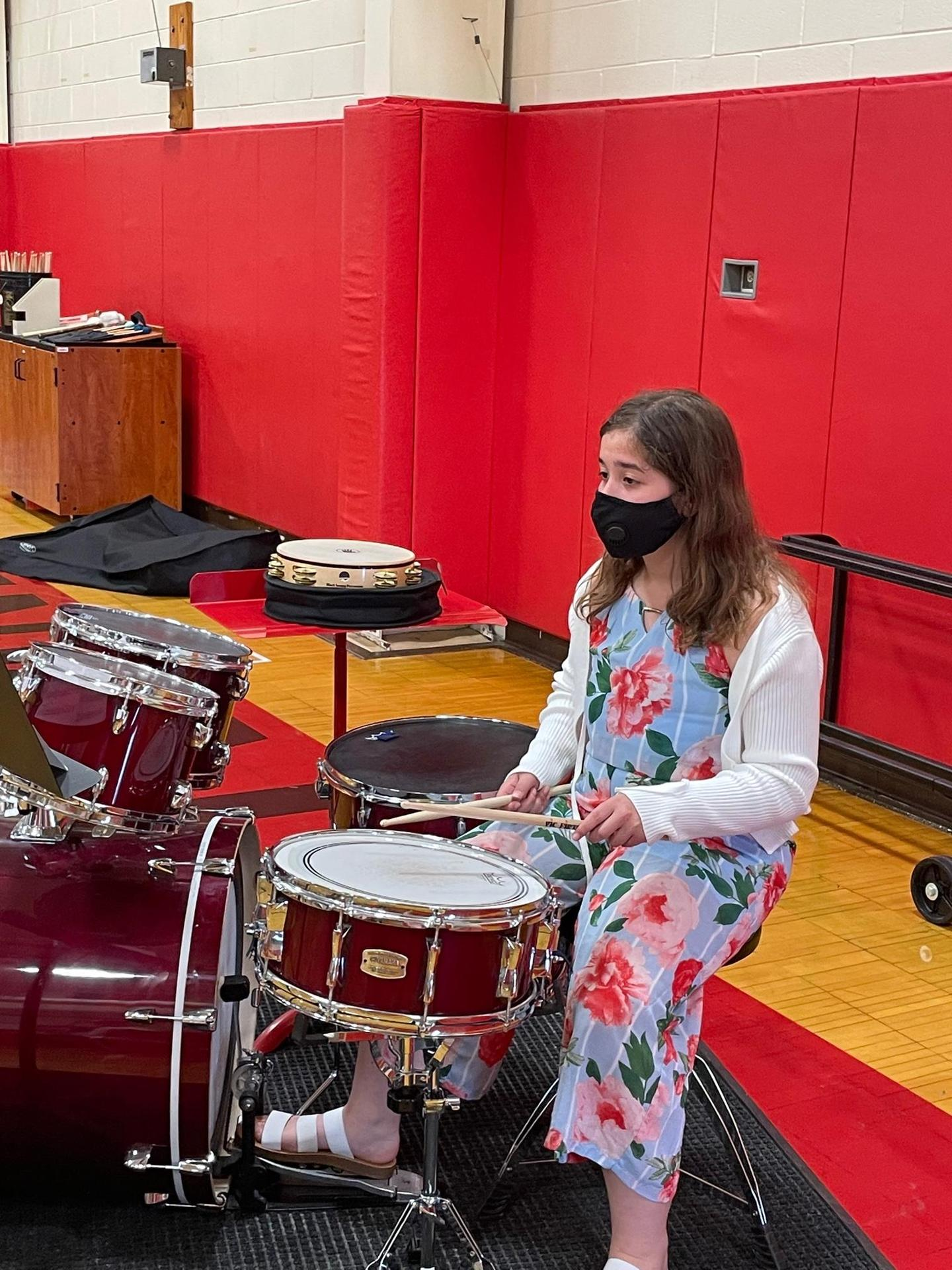 A student playing drum set in the Benjamin gym