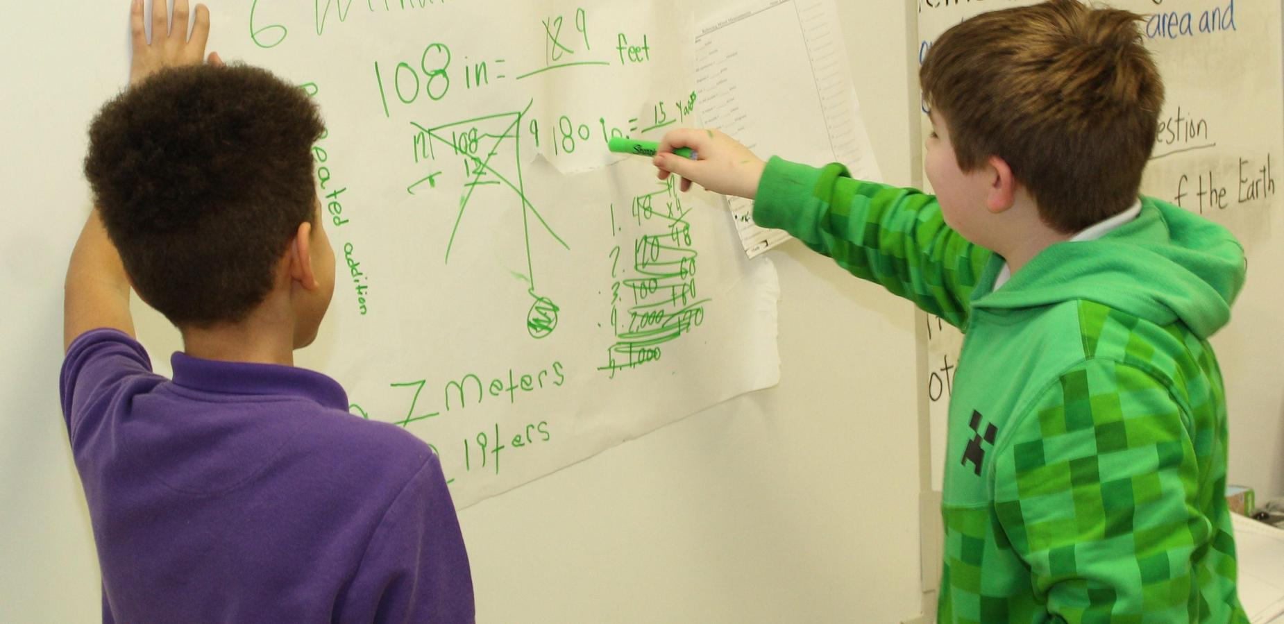 Two boys working a math problem on the board.