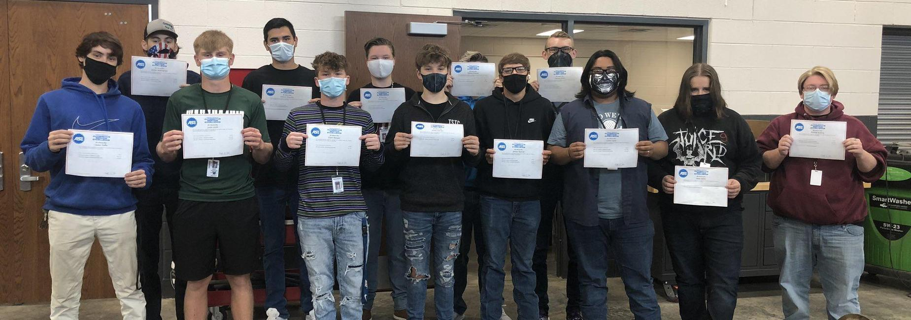 13 young men in a row holding certificates wearing facemasks