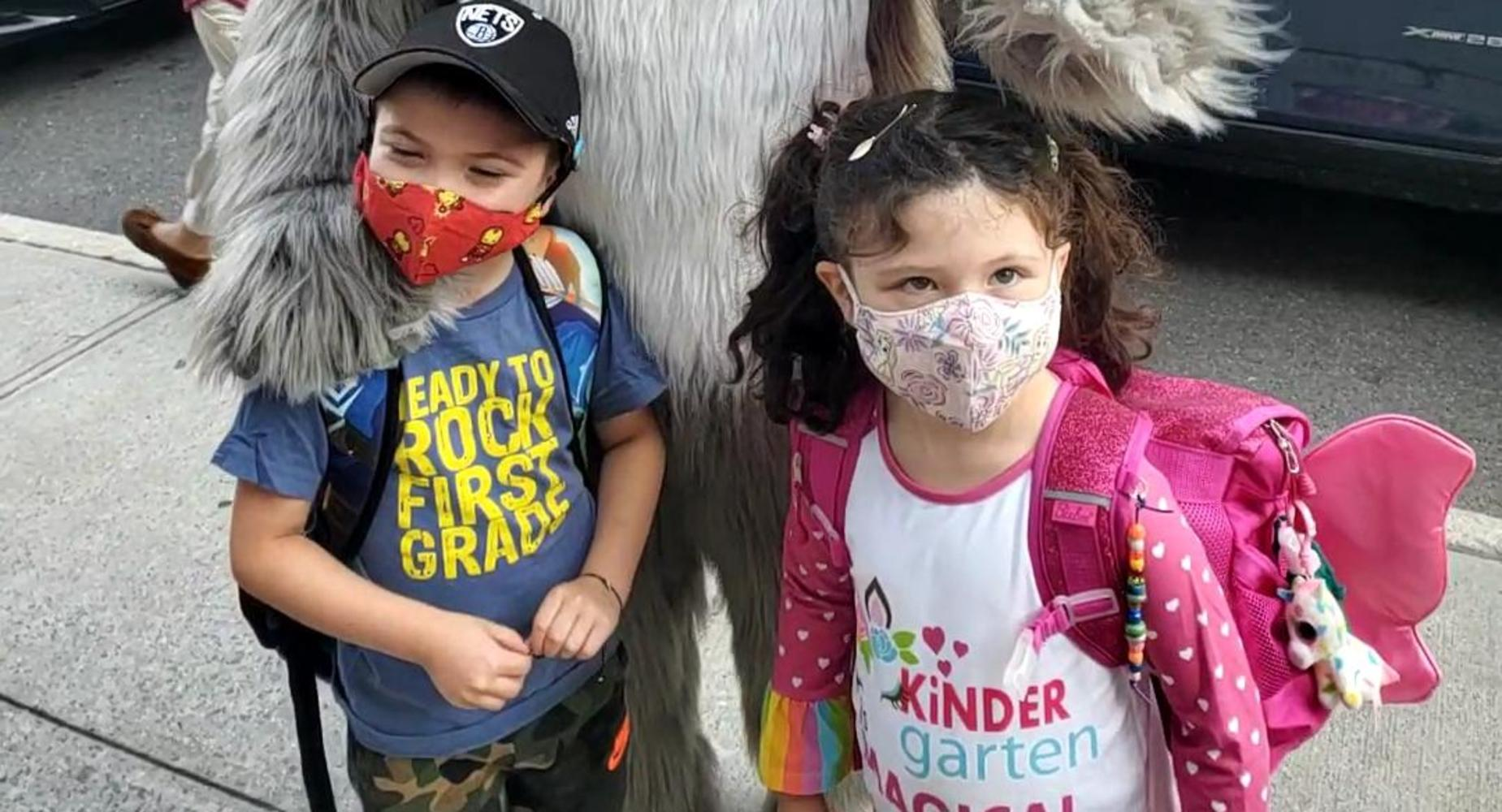boy wearing hat and girl wearing pink and white shirt and pink backpack in front of husky mascot