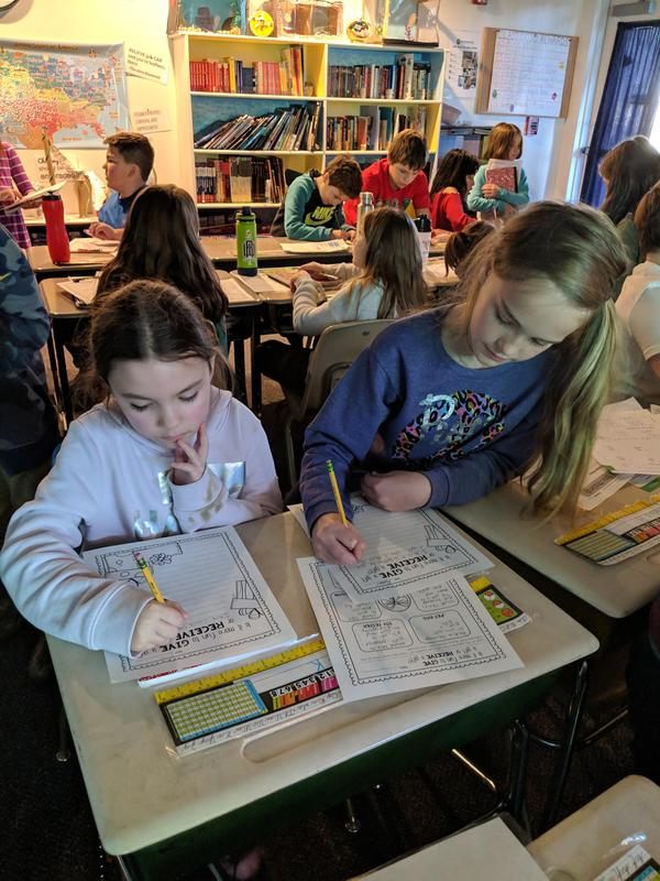3rd and 5th grade students writing together