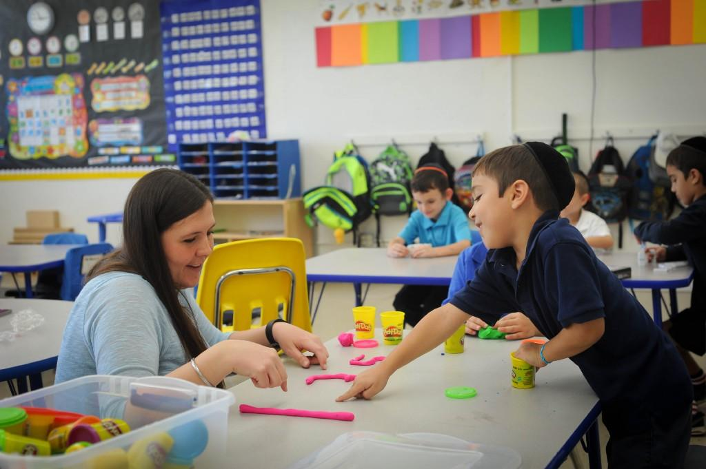 Ms. Jamie making letters out of play dough with the kindergarten boys