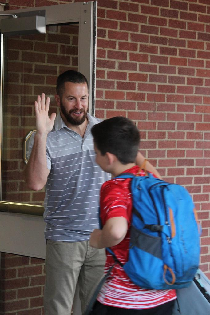 Teachers greeting students at the door.