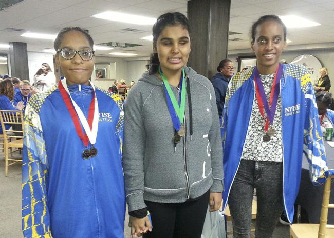 3 girls smiling with their medals