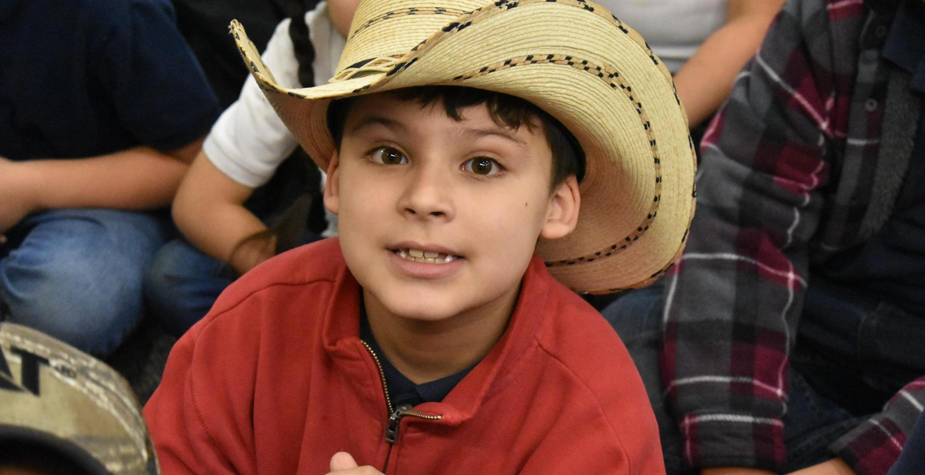 A little boy wearing a cowboy hat for hat day.