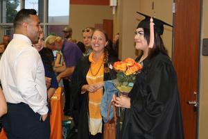 Graduate holding flowers