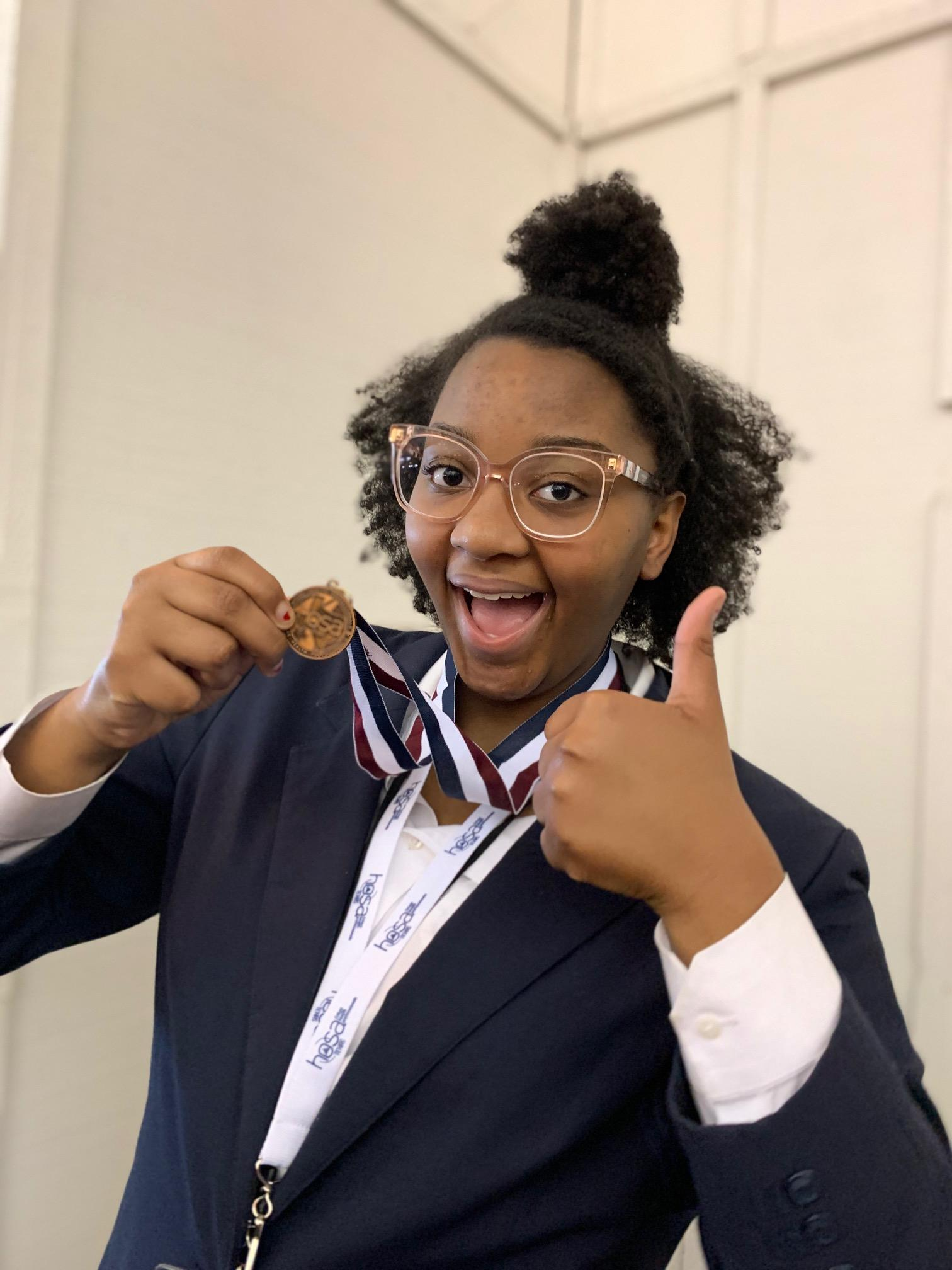 girl gives thumbs up holding medal she earned