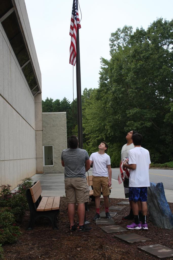 Four students raise the American flag on the first day of school at WECHS
