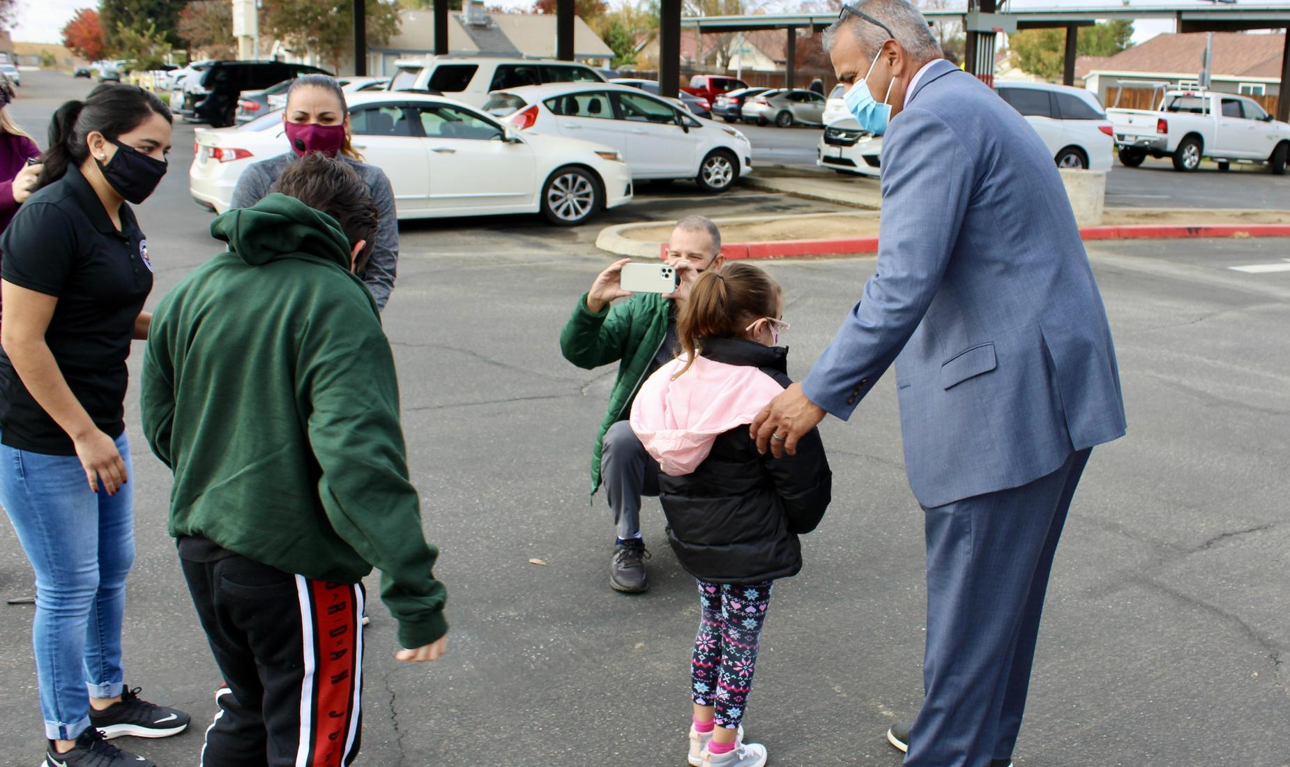Central Unified Superintendent Alvarado assists a Saroyan student with her new coat.