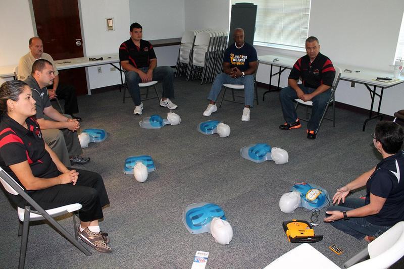 nurse showing several people how to use an AED