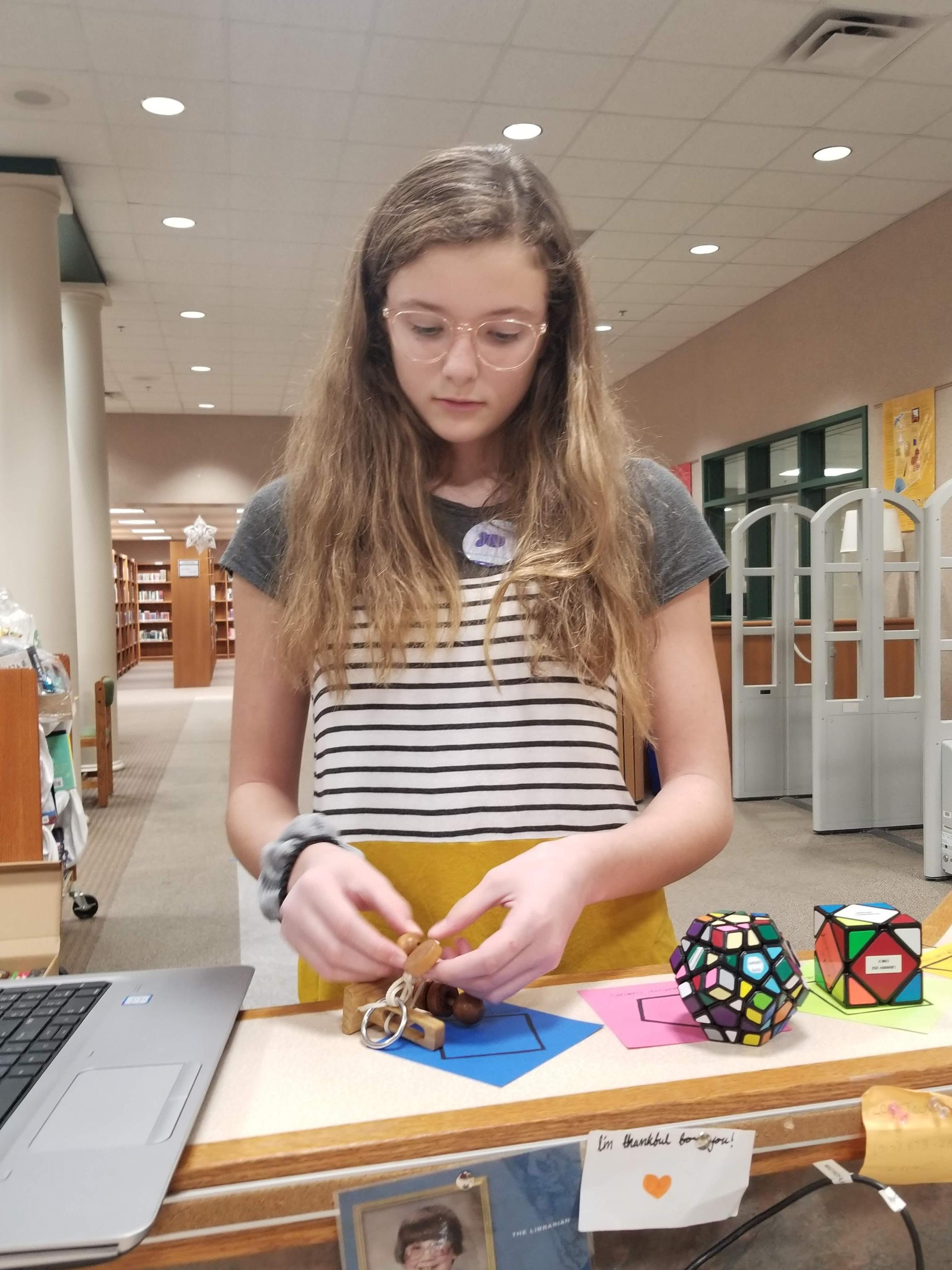 A girl looks at a 3D puzzle in her hands