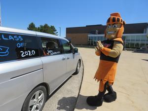 The TK Trojan mascot delivers the graduation supplies to seniors.