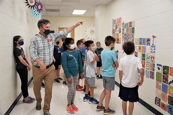 Mr Oliver leads fourth graders on a tour of middle school.