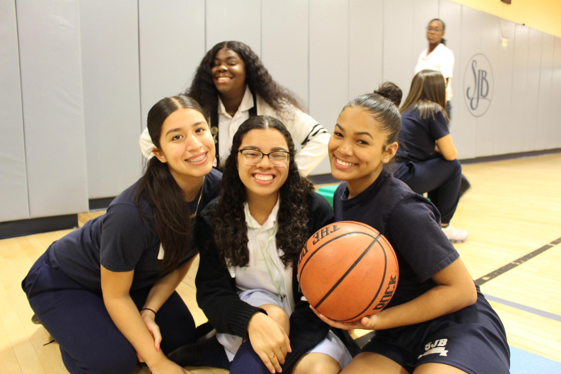 three girls in blue gym cloths one holds a basketball. one girl in white sweater in the background