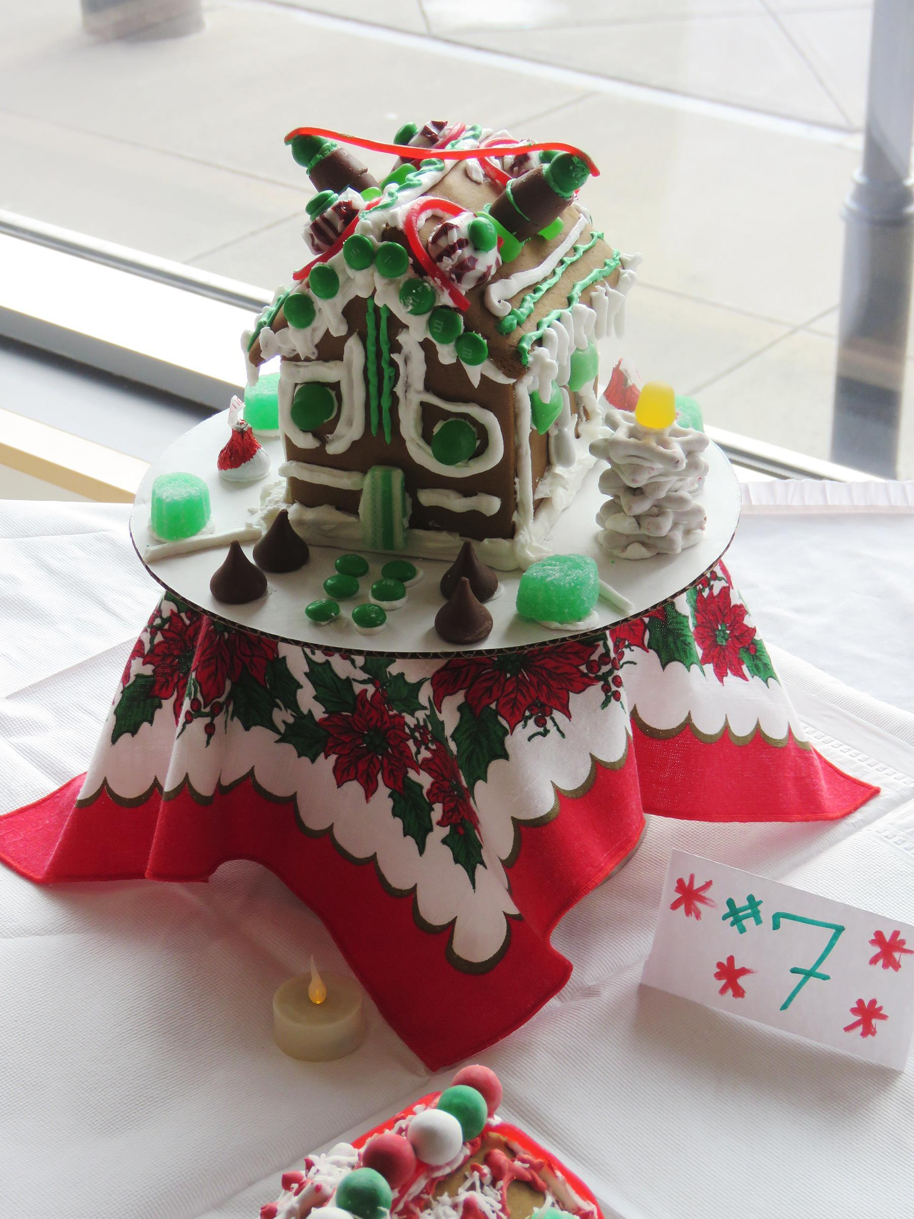 An intricately-decorated gingerbread house on a pedestal