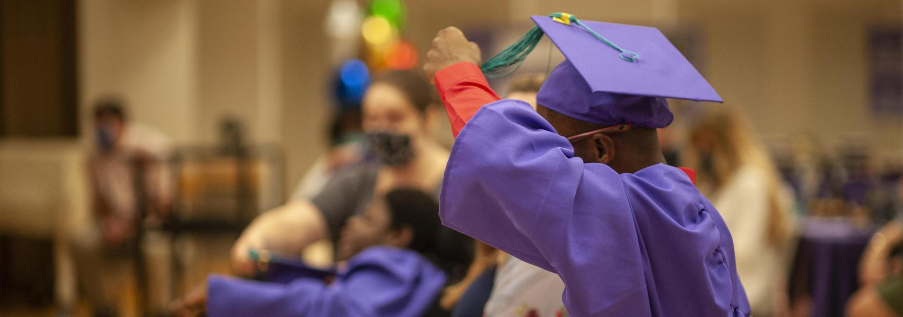 Student in the secondary program move tassel on cap to signify graduating.