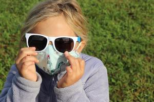 close up of little girl with sunglasses on