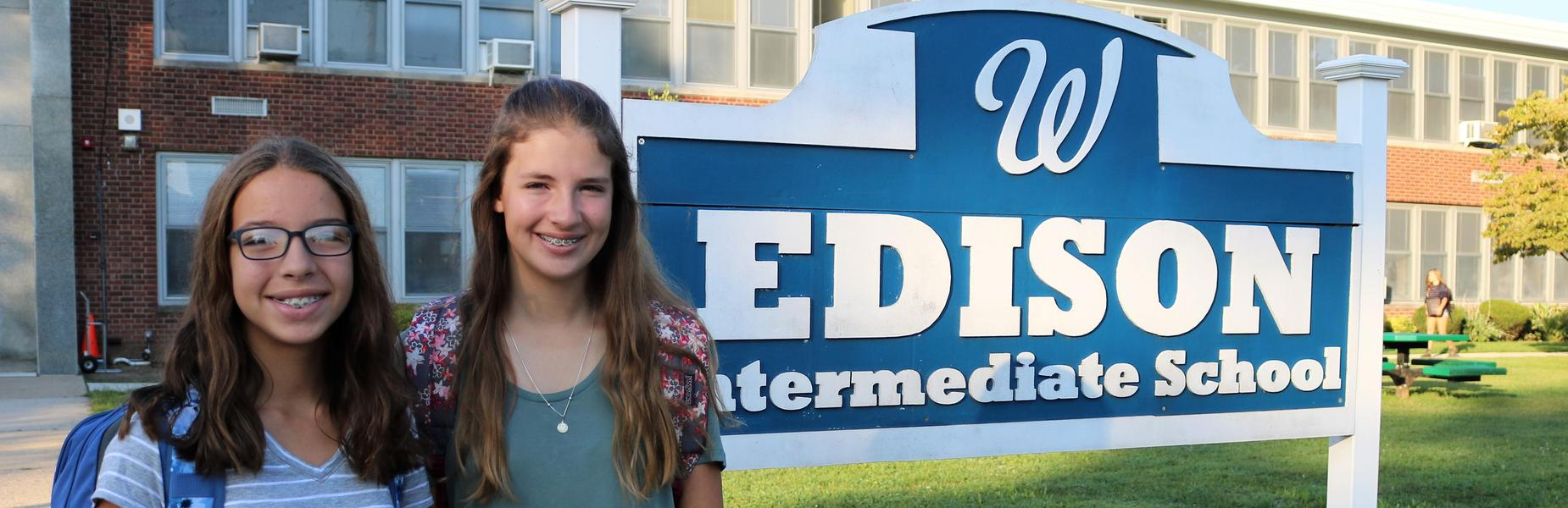 Two sisters pose for a picture in front of Edison Intermediate School sign on first day of school.