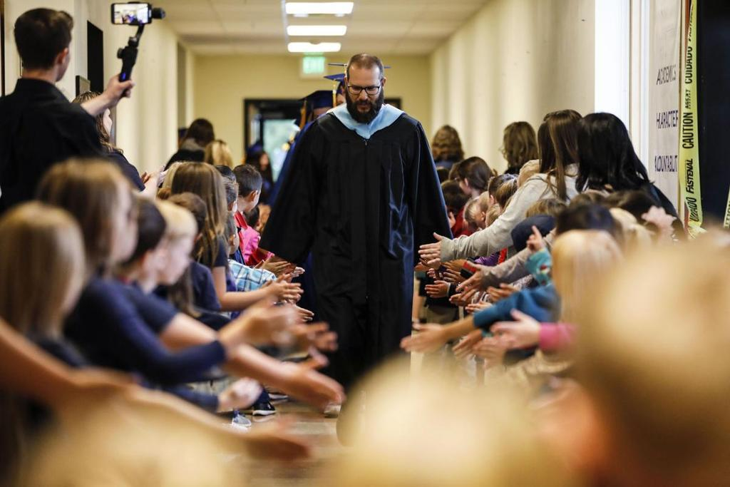 Mr. Collins leading 2019 graduates through the halls before Commencement