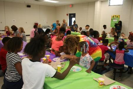 A group of students, teachers, and parents painting rocks for Tifton Rocks.
